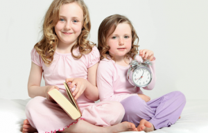 one girl holding a book and another girl holding a clock