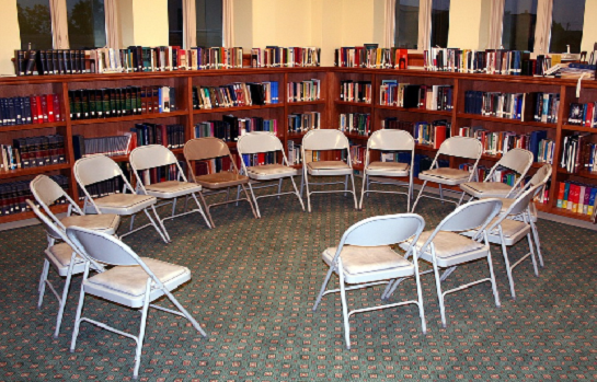chairs in a circle with bookshelves in the back