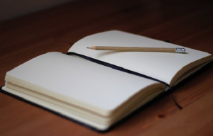 open blank book with a pencil