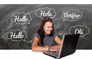 chalkboard with hello written in different languages with a girl on a laptop smiling