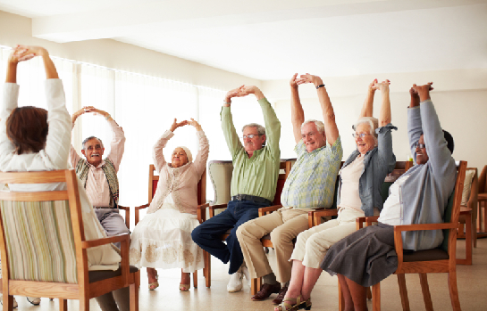 senior citizens sitting in chairs and stretching arms above their heads